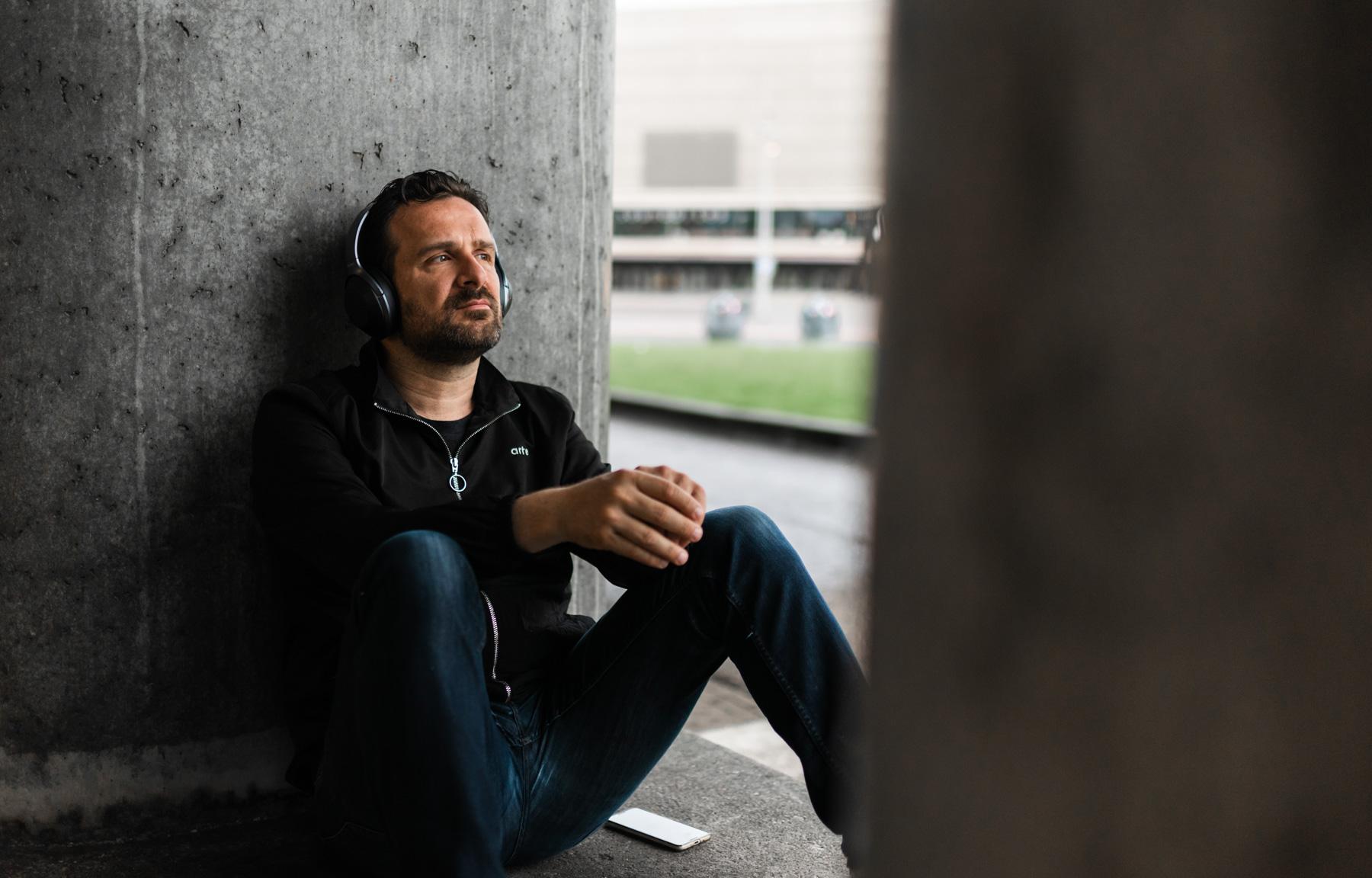 Merlijn Hoek zit met rug tegen de muur en luistert muziek via headset