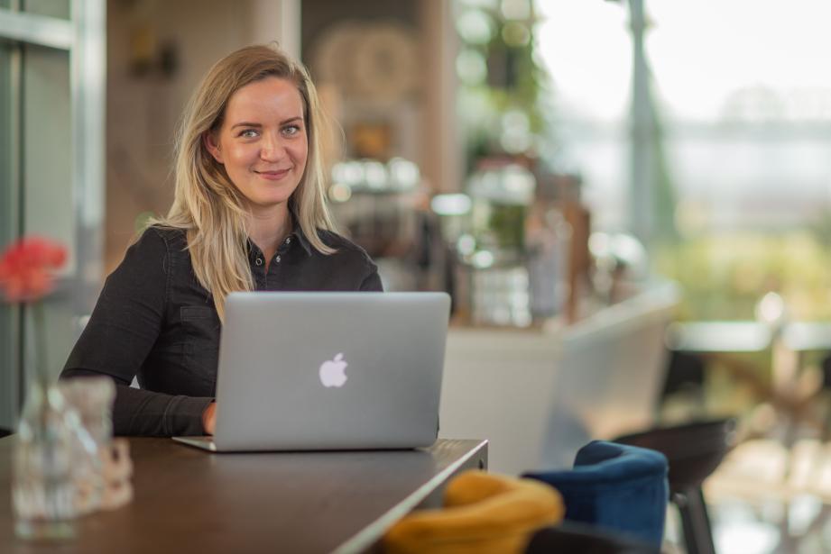 Eva van der Niet achter laptop in koffiecorner